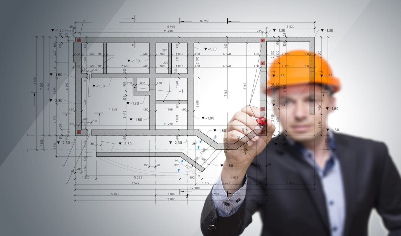 acoustical contractorn in hard hat drawing on blueprint - construction design build